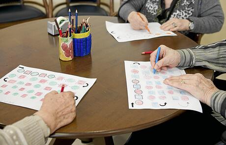 Varios ancianos en una residencia haciendo terapia ocupacional. | HA